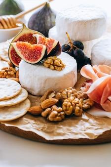 Camembertkäse, feigen, jamon, honig und trauben. käseplatte auf marmorhintergrund