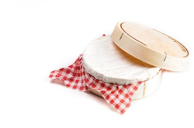 Camembertkäse in der holzkiste auf weiß