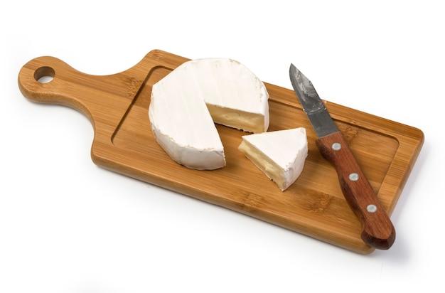 Camembertkäse mit messer auf holzbrett