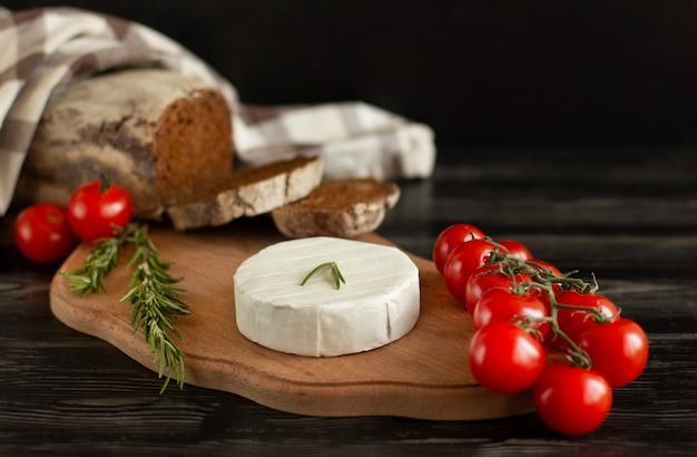 Camembertkäse mit roggenbrot, nüssen, kirschtomaten und rosmarin auf einem hölzernen brett