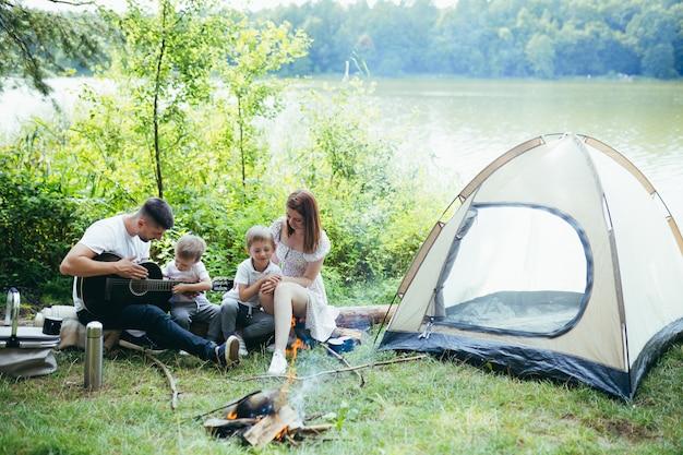 Camping am see im wald. glückliche familienvatermutter und kleine kinder, die am feuer und im zelt in der natur sitzen. gemeinsame freizeit im urlaub verbringen. draußen. eltern mit kindern. vater spielt gitarre. lager