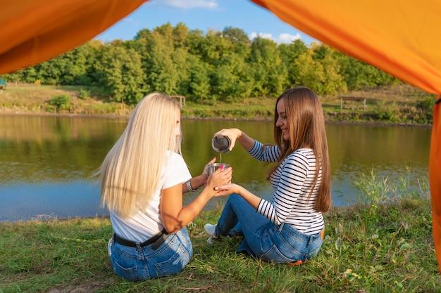 Camping am seeufer bei sonnenuntergang, blick aus dem zelt. zwei wunderschöne mädchen genießen die natur und trinken heißen tee vor dem zelt