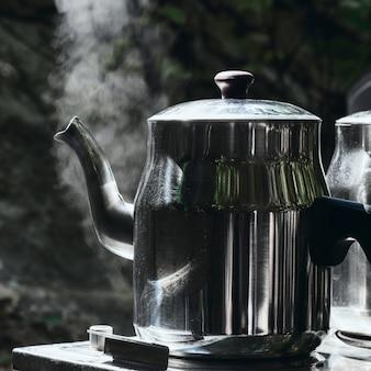 Camping camp ferien konzept. zwei teekannen mit heißem tee