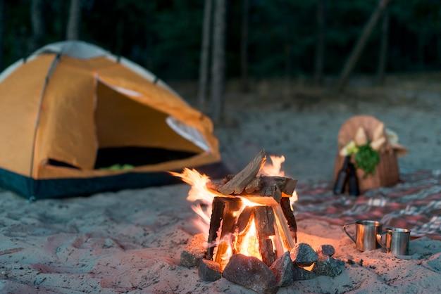 Camping feuer brennt in der nähe des zeltes