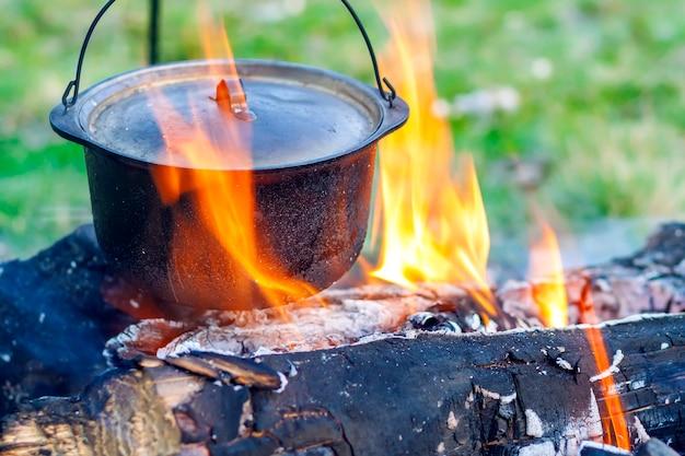 Camping geschirr - topf auf dem feuer auf einem campingplatz im freien