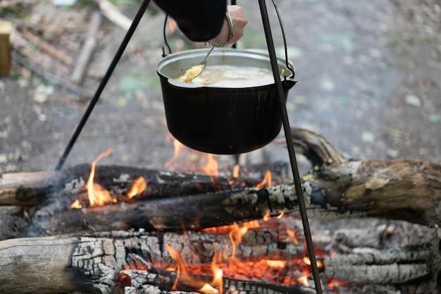 Camping im freien. kochmelone hing auf stativ über brennendem feuer auf dem hintergrund von gras und abgesplittertem brennholz