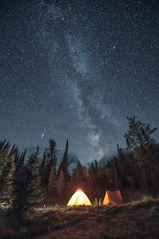 Camping im kiefernwald mit milchstraße und sternschnuppe im assiniboine provincial park