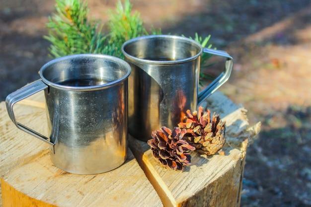 Camping in der natur. touristische eisenbecher im wald mit kräutertee, der auf einem feuer gekocht wird. erholung im freien.