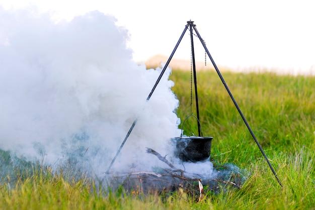 Camping küchengeschirr - topf auf dem feuer auf einem campingplatz im freien mit dicken weißen rauch