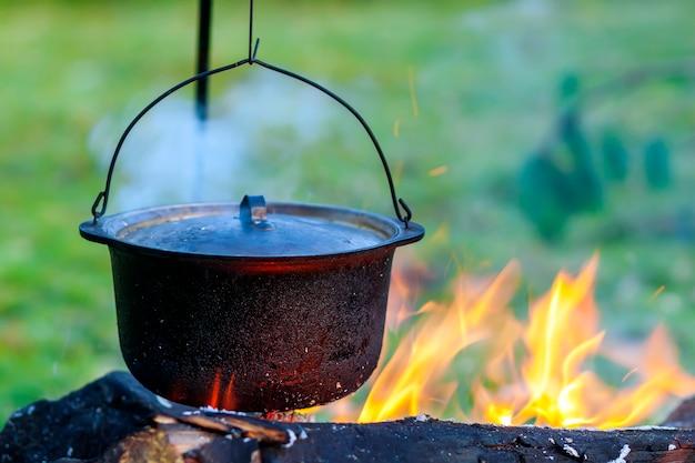 Camping küchengeschirr - topf auf dem feuer auf einem campingplatz im freien
