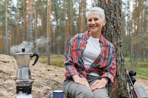 Camping lebensstil im wald. fröhliche euroepan-frau mittleren alters, die auf dem boden unter kiefer sitzt, um tee zu machen, kochendes wasser im kessel auf gasherdbrenner, freudigen glücklichen gesichtsausdruck habend
