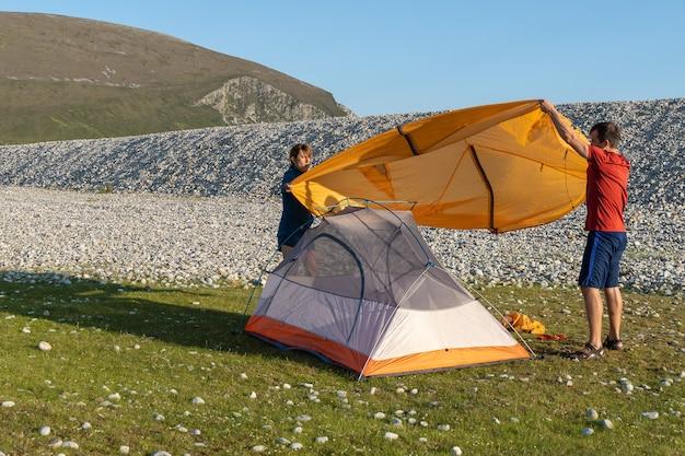 Camping-leute im freien lifestyle-paar, das ein zelt am felsigen strand der natur aufstellt.