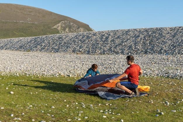 Camping-leute im freien lifestyle-paar, das ein zelt am felsigen strand der natur aufstellt?