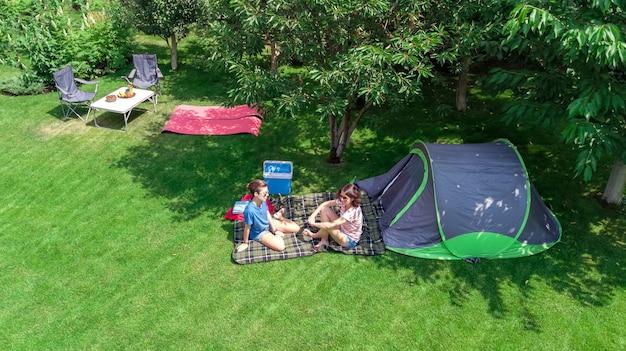 Camping-luftbild von oben mutter und tochter, die spaßzelt und campingausrüstung unter baumfamilienurlaub im lager im freienkonzept haben