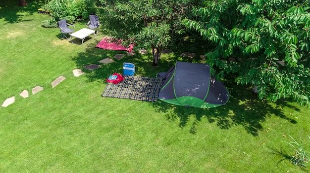 Camping-luftbild von oben zelt und campingausrüstung unter baumfamilienurlaub im camp im freien konzept