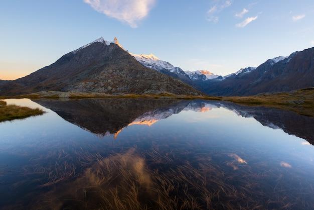 Camping mit zelt in der nähe von hochgelegenen see in den alpen. reflexion des schneebedeckten gebirgszugs und des szenischen bunten himmels bei sonnenuntergang. abenteuer und erkundung.