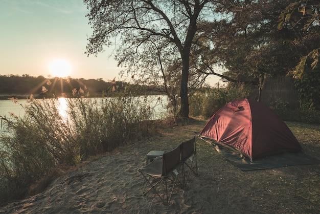 Camping mit zelt, stühlen und campingausrüstung. sonnenaufgang über okavango river, grenze namibias botswana. abenteuerreisen und outdoor-aktivitäten in afrika. getönten bild, vintage-stil.
