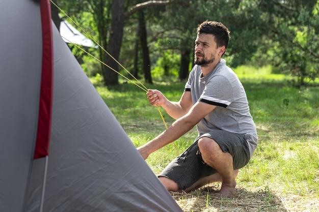 Camping, reisen, tourismus, wanderkonzept - junger mann, der ein zelt im wald aufstellt.