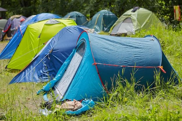Camping rucksacktouristen in waldlichtung an sonnigen sommertagen, viele moderne mehrfarbige zelte sind auf gras nahe beieinander aufgestellt.