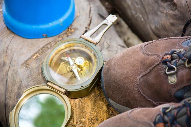 Camping- und wanderausrüstung mit schuhen und kompass im freien