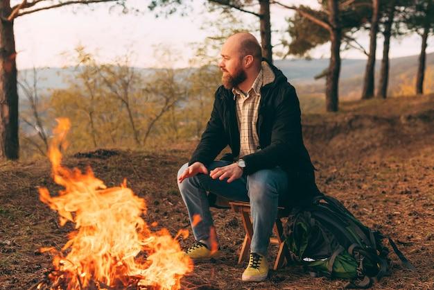 Camping, wandern, lifestyle. hipster wanderer, der nahe lagerfeuer im wald sitzt