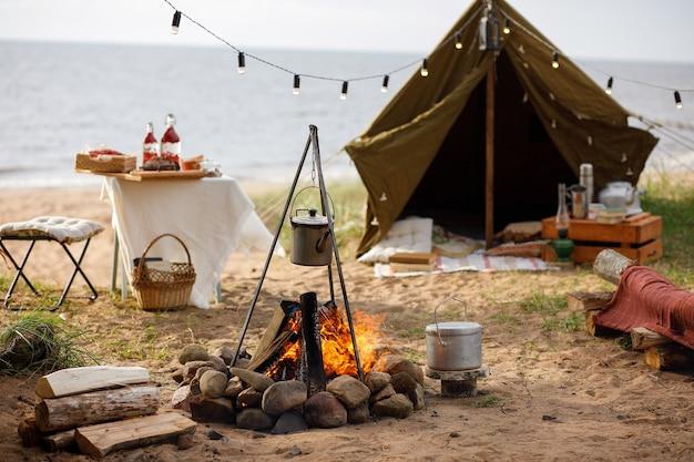 Campingplatz mit lagerfeuer am seeufer.