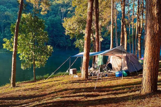 Campingzelt mit lebensstil der ausrüstung im freien morgensonnenlicht mit großem campingzelt nahe fluss.