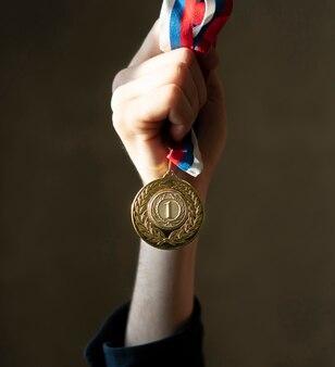 Campion hand mit einer goldenen medaille, einfaches gewinner-glückskonzept