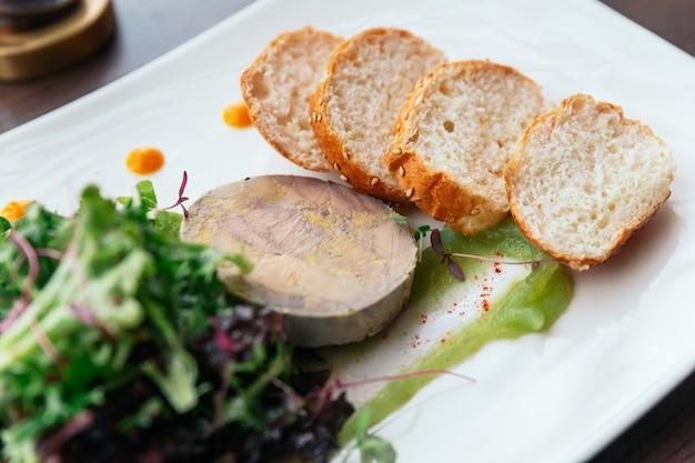 Canape mit gänseleberpastete und salat serviert mit weißwein.