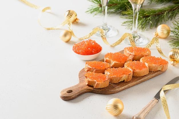 Canape mit rotem kaviar serviert auf schneidebrett für weihnachtsfeier des neuen jahres