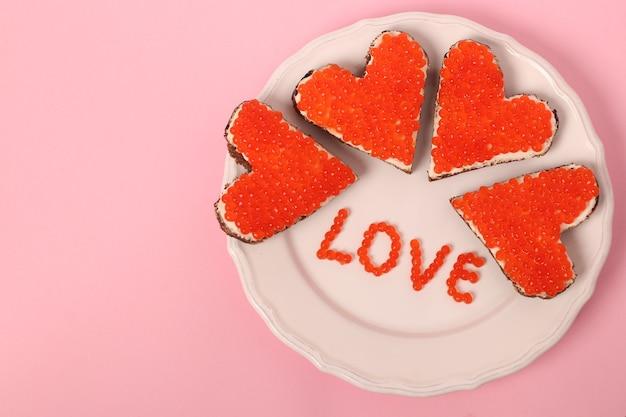 Canape mit rotem kaviar und frischkäse in form eines herzens zum valentinstag auf rosa hintergrund. von oben betrachten