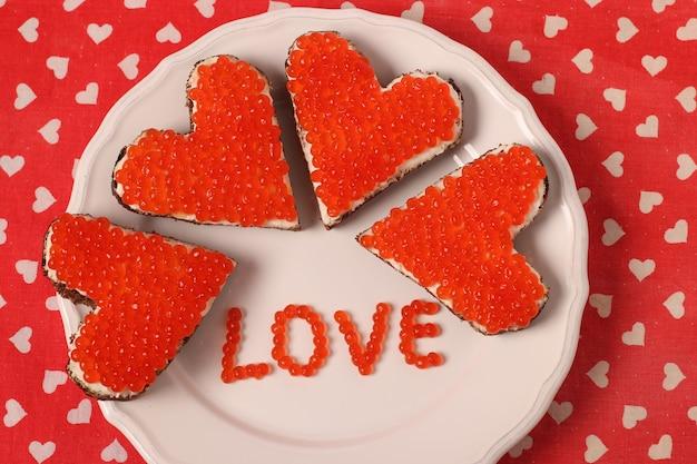 Canape mit rotem kaviar und frischkäse in form eines herzens zum valentinstag. von oben betrachten
