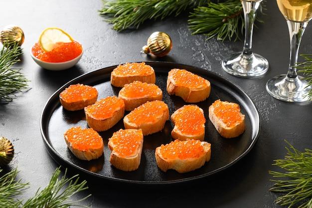 Canape mit rotem lachskaviar für silvester oder weihnachtsfeier auf schwarzem hintergrund. festliches feiertagsessen. leckere vorspeise und champagner. platz kopieren.
