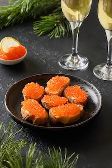 Canape mit rotem lachskaviar für silvester oder weihnachtsfeier auf schwarzem hintergrund. festliches feiertagsessen. leckere vorspeise und champagner.