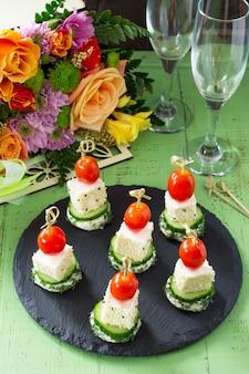 Canape mit weißbrot, gurke, feta-käse und kirschtomaten auf einem festlichen tisch. valentinstag oder hochzeit.