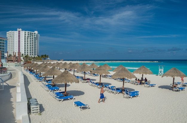 Cancun, mexico. strohsonnenschirm am strand von cancun, urlaubsruhe, blaues karibisches meer.