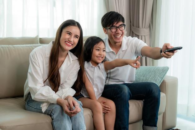 Candid der glücklichen asiatischen familie genießen wochenendaktivität, indem sie zu hause fernsehprogramm aufpassen.