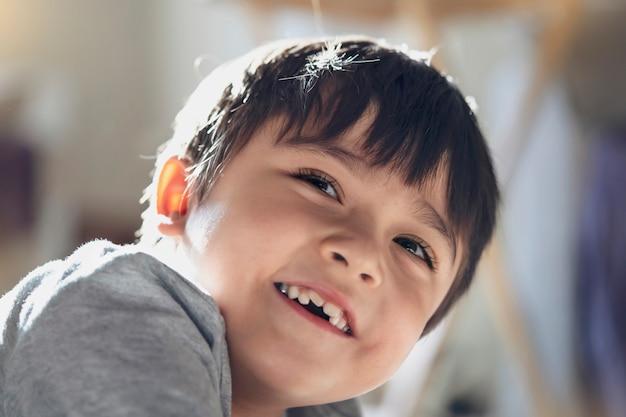 Candid schoss glückliches kind, das mit lächelndem gesicht aufblickte