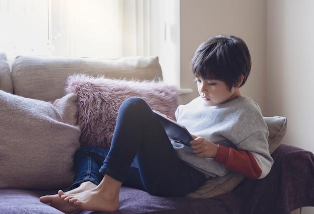 Candid schoss niedlichen kleinen jungen, der cartoons auf tablette, porträt des schulkindes beobachtet, das auf sofa mit ernstem gesicht sitzt, das spiele auf smartphone spielt. warme und gemütliche szene in pastellton