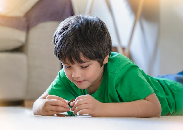 Candid shot glückliches kind, das auf dem boden liegend liegt und mit plastikspielzeug spielt, positives kind, das allein auf teppich im wohnzimmer spielt, niedlicher junge, der am wochenende zu hause entspannt, fantasie und entwicklung der kinder