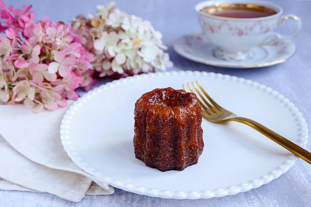 Canele, französische konditorei, auf einem weißen teller, mit einer gabel, einer tasse tee und hortensienblüten