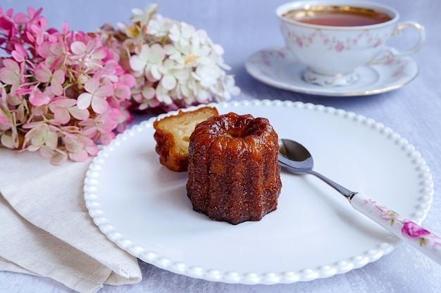 Canele, französische süßwaren, auf einem weißen teller, mit einem geschnittenen stück, einem löffel, einer tasse tee und blumen