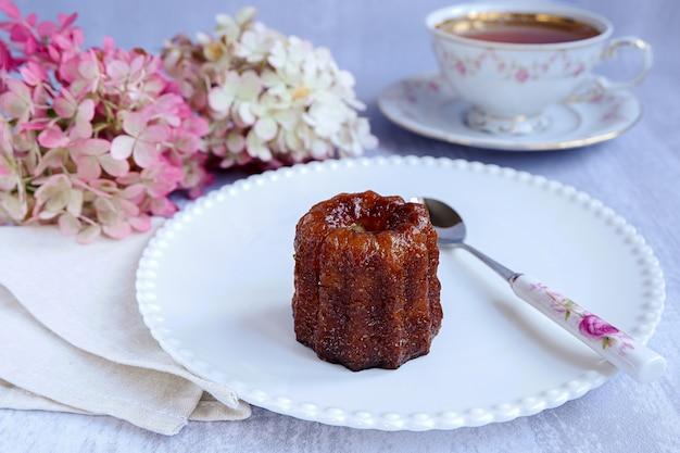 Canele, französische süßwaren, auf einem weißen teller, mit einem löffel, einer tasse tee und blumen