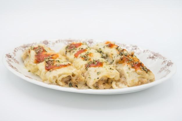 Canelones (cannelloni) mit fleischgefüllten nudeln und käse und tomaten auf einem teller