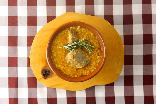 Canjiquinha, ein traditionelles gericht der brasilianischen küche, hergestellt aus schweinerippchen und zerkleinertem mais, in einer keramikschale auf einem rustikalen holztisch. nahaufnahme