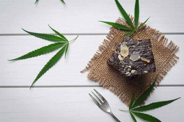 Cannabis brownies und cannabisblätter auf stoff gelegt
