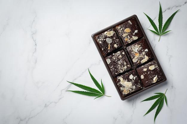 Cannabis brownies und cannabisblätter auf weißen boden gelegt