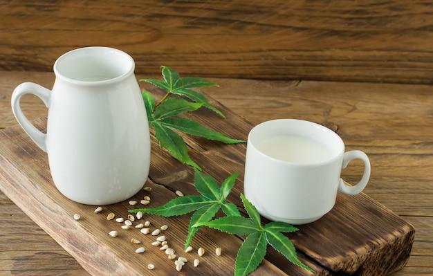 Cannabis pflanzliche vegane gluten- und laktosefreie milch und cannabisblätter auf holztisch.