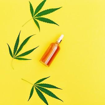 Cannabis-schönheitsprodukte aus hanfcreme und grünen blättern auf gelb