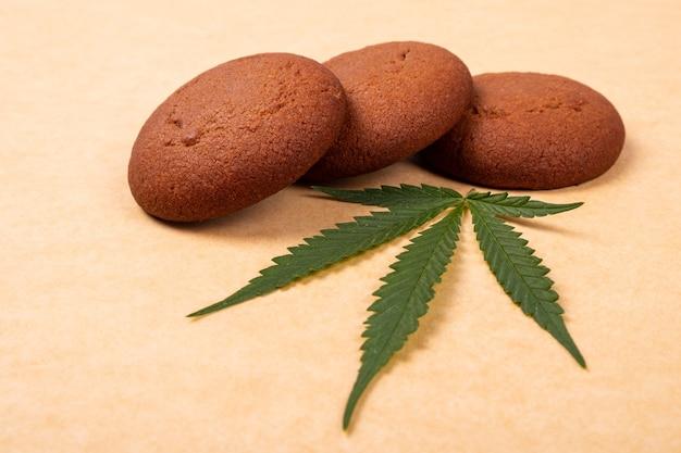 Cannabis-süßigkeiten, marihuana-keks und grünes blatt schließen oben.